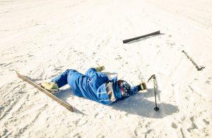 Jazda na nartach - narciarz leżący na śniegu po upadku.